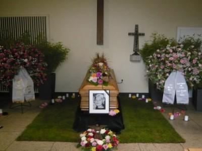 Sargschmuck in dekorierter Trauerhalle mit Rollrasen und Leihpflanzen