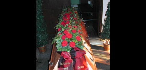 Sargschmuck mit roten Rosen